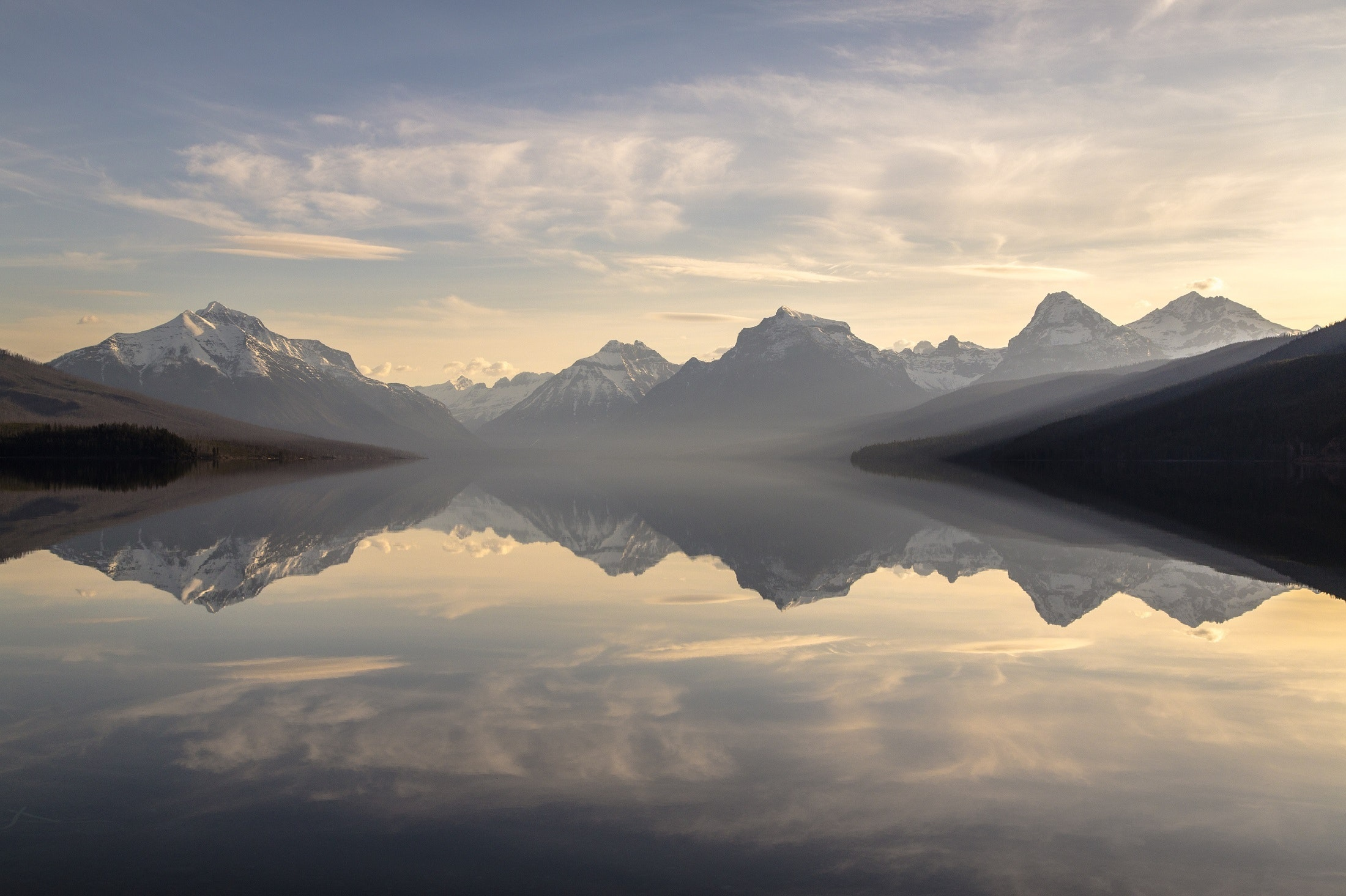 Clouds and mountains reflected in a calm lake